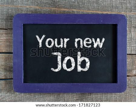 Your new Job written on blue framed chalkboard on wooden background - stock photo