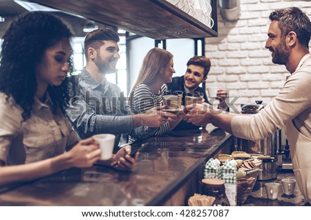 Your order is ready! Side view of barista passing coffee cups to his customer while standing at bar counter - stock photo