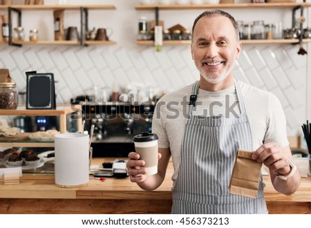 Your order please. Happy and cheerful male cafe worker in apron holding coffee to go and little lunch paper bag - stock photo