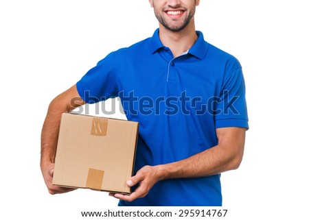 Your package is in safe hands. Cropped image of young courier holding a cardboard box and smiling while standing against white background - stock photo