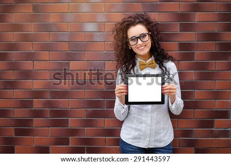 Your text here. Attractive young woman with curl hair showing screen of tablet computer against brick wall. - stock photo