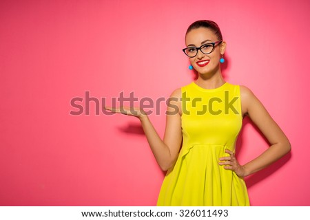 Your text here. Colorful studio portrait of young smiling woman pointing copy space. Pink background. - stock photo