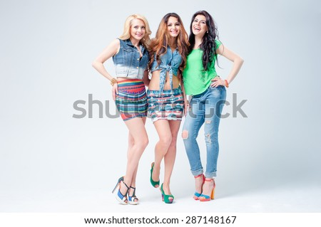 Youth and fashion. Three sexy chic young women in summer fashion standing arm in arm showing off their long shapely slender legs. - stock photo