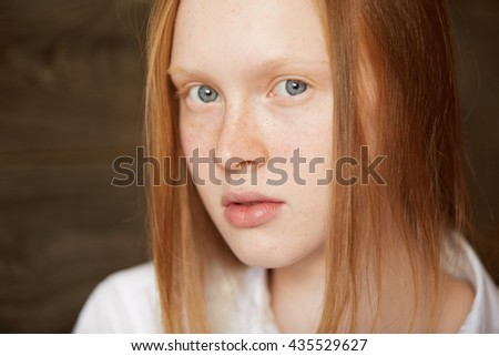 Youth and skin care concept. Highly-detailed portrait of beautiful Caucasian teenage girl with ginger hair and perfect clean skin with freckles, posing against wooden wall background in white shirt - stock photo