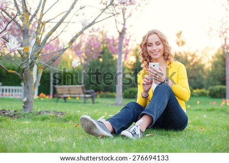 Youth and technology. Attractive young woman using smartphone while sitting on grass in spring park. - stock photo