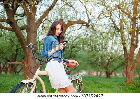Youth and technology. Attractive young woman with bicycle using smartphone in green park. - stock photo