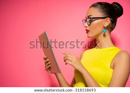 Youth and technology. Colorful studio portrait of young attractive brunette woman using tablet computer against pink wall. - stock photo