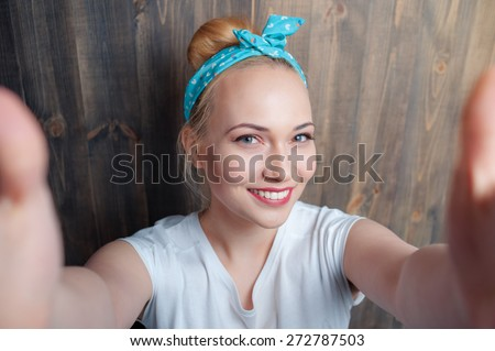 Youth and technology. Young attractive smiling woman taking selfie on camera against wooden wall. - stock photo