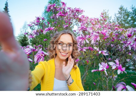 Youth and technology. Young smiling woman taking selfie  while standing in blossom garden. - stock photo