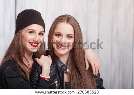 Youth and urban fashion. Attractive twins sisters. Close up of  two beautiful smiling young women standing together against grey wooden background. - stock photo
