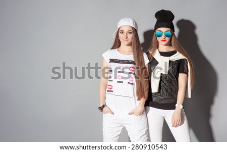 Youth and urban fashion. Attractive twins sisters. Two beautiful young women standing together against grey wall. - stock photo