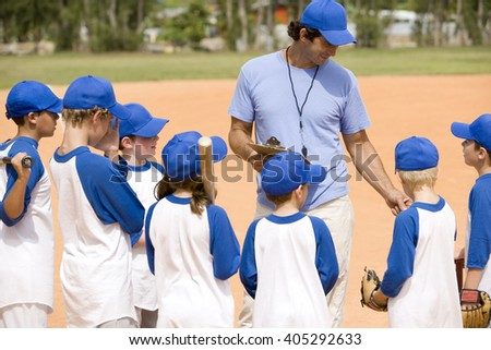 Youth baseball team and coach on pitch - stock photo