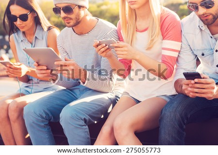 Youth culture. Four young people sitting close to each other and looking at their gadgets - stock photo