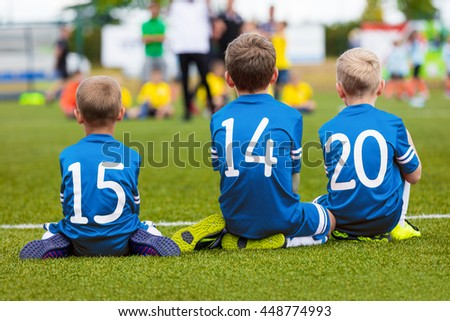 Youth football soccer team sitting together on field and watching soccer match. Young boys as reserve players on bench supporting blue team - stock photo