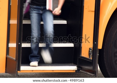Youth getting off of school bus - stock photo