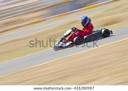 Youth Go Kart Racer on track.  Shot is panned to emphasize speed. - stock photo