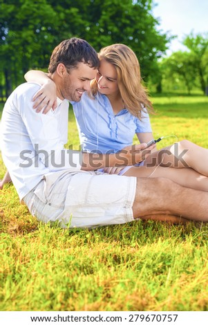 Youth Lifestyle Concept:Relaxing Caucasian Coiple Sitting Together Outdoors. Listening to Music in Headphones. Vertical Image - stock photo
