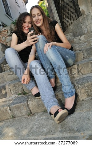 Youth lifestyle - two smiling friends (girls) siting on stairs outdoors with mobile phone - stock photo