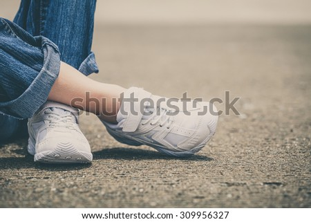 youth sneakers on girl legs on road during sunny  summer day. - stock photo