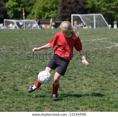 Youth Soccer Player Ready to Kick Ball with ball in air - stock photo
