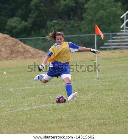Youth Teen Goalie Kicking Soccer Ball - stock photo