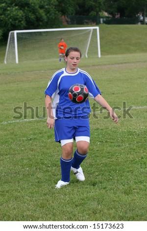 Youth Teen Soccer Player Ready to Kick Ball while Ball in Air - stock photo