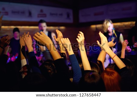 youth waving hands on concert in night club - stock photo