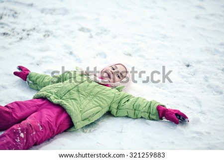Youthful girl playing outside in snow - stock photo