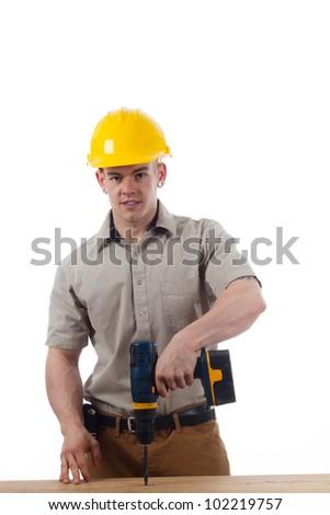 Youthful Handy Man drills a hole - stock photo