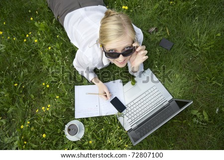 ypung woman working outside on computer - stock photo