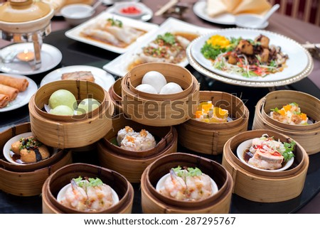 yumcha,The Arrangment of various dim sum in bamboo steamer with chinese bun , pao , bao zi , steamed dumpling , shumai on table in chinese restaurant - stock photo