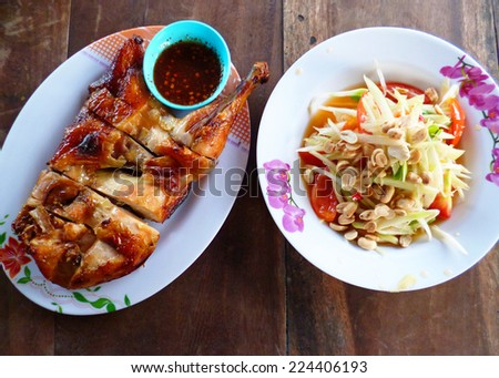 Yummy authentic Local thai food Somtum and Gaiyang, Papaya spicy salad and griled chicken with purple orchid image decorated  - stock photo