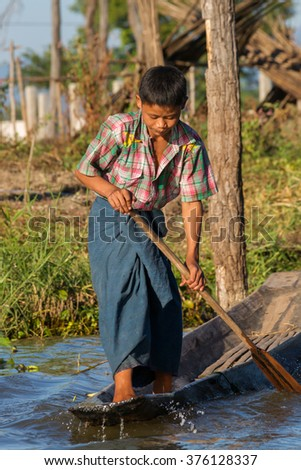 Ywama, Myanmar - November 23: A young boy exercising the distinctive local leg rowing style used by the locals around the famous Inle Lake. Ywama, Shan State, Myanmar on November 23, 2014 - stock photo