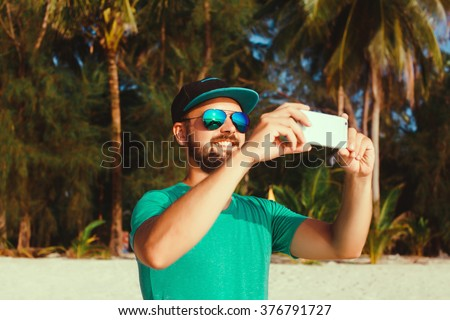 yyoung handsome man with beard and mustache in baseball cap, with a smartphone in hand, hipster style, outdoor portrait, close up,posing on the beach in a t-shirt and denim shorts, make a selfie  - stock photo