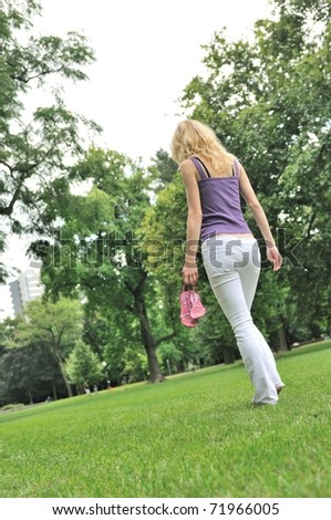 Yyoung woman holding her shoes and walking barefoot on grass in park - rear view - stock photo
