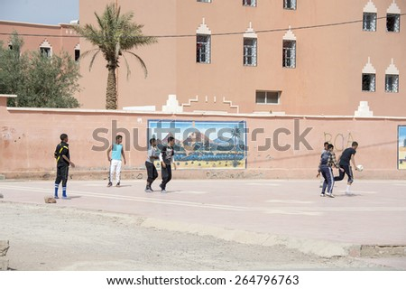 ZAGORA, MOROCCO, MARCH 8, 2014. School boys playing football in the main street of Zagora, in Morocco, on March 8th, 2014. A wall painting in the wall. - stock photo