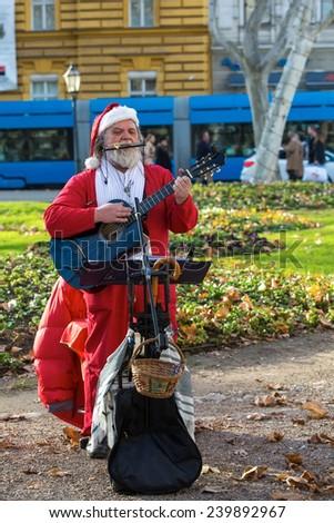 ZAGREB, CROATIA - DECEMBER 24, 2014: Senior man dressed as Santa Claus, playing guitar, on Zrinjevac park. Zrinjevac is spread over 12540 sq meters in city center. - stock photo