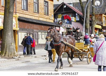 ZAKOPANE, POLAND - MARCH 06, 2016: Coachman is carrying tourists along Krupowki street in main shopping area and pedestrian promenade in the city center of Zakopane - stock photo