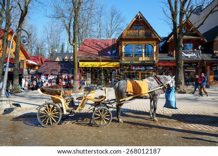 ZAKOPANE, POLAND - MARCH 09, 2015: Harnessed Horse stands, at the Krupowki street, the main shopping area and pedestrian promenade in the downtown  - stock photo