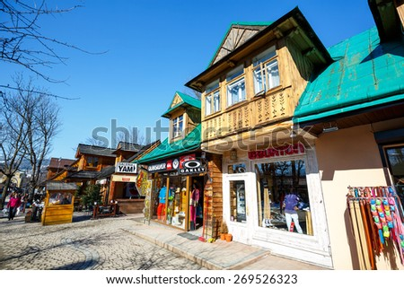 ZAKOPANE, POLAND - MARCH 09, 2015: Residential and commercial buildings built of wood at the turn of the 19th and 20th century, located at Krupowki, the main pedestrian street in the city  - stock photo