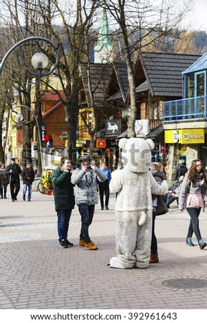 ZAKOPANE, POLAND - MARCH 09, 2016: Unrecognized man portrays the role of a teddy bear, tourists eagerly wants to have photos with him. It is an attraction on the famous street Krupowki - stock photo