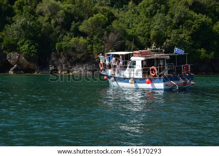 ZAKYNTHOS, GREECE - JULY 5, 2015: People on fishing boat have spotted a caretta sea turtle swimming in the shallows close to Keri beach in the national sea park of Zakynthos, Greece. - stock photo