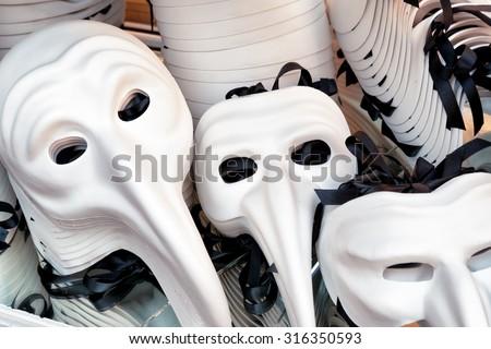 Zanni authentic and original Venetian white eye masks for Carnival in souvenir shop on the Rialto Bridge. Venice is a popular tourist destination of Europe. - stock photo