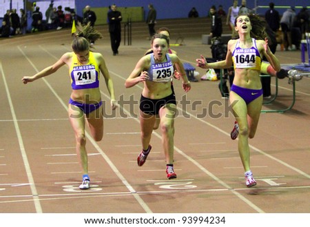 ZAPORIZHIA,UKRAINE - JAN 30: (L-R) Moroz Ulia, Sidor Oleksandra and Klimuk Katerina run across the finish line during the 400 meters race on Ukainian Junior Track and Field Championships on January 30, 2012 in Zaporizhia, Ukraine - stock photo