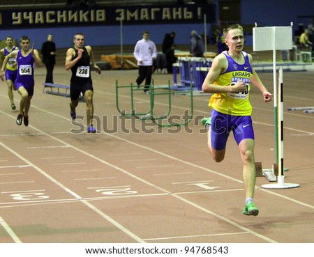 ZAPORIZHIA,UKRAINE - JAN 31: Pozdnikov Aleksei runs to the finish of the 400 m. race on Ukrainian Junior Track and Field Championships on January 31, 2012 in Zaporizhia, Ukraine - stock photo