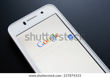 ZAPORIZHZHYA, UKRAINE - NOVEMBER 07, 2014: White Smart Phone with Google Search on Screen on the Black Table. - stock photo