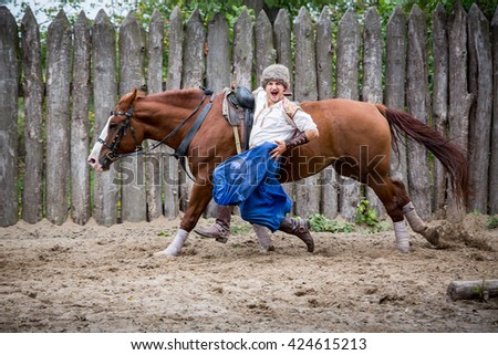 ZAPOROZHYA, UKRAINE -SEPTEMBER 22, 2013- Cossack rider performing horse riding skills in Ukraine.  Historically, Cossacks were known as exceptional horsemen. - stock photo