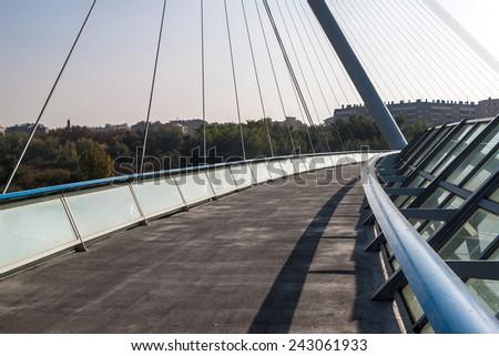 ZARAGOZA, SPAIN - NOVEMBER 1: Pedestrian bridge over Ebro river in Zaragoza, Spain on November 1, 2014. Bridge was built in 2008 for the international EXPO. - stock photo