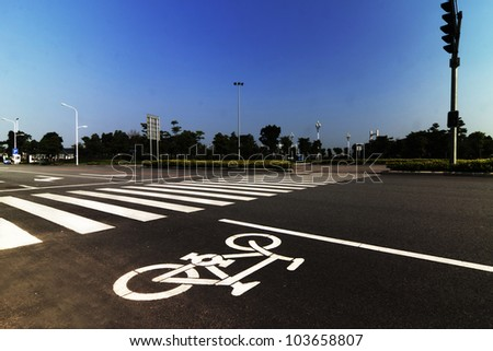 zebra crossing and bicycle sign forming abstract design on the street - stock photo