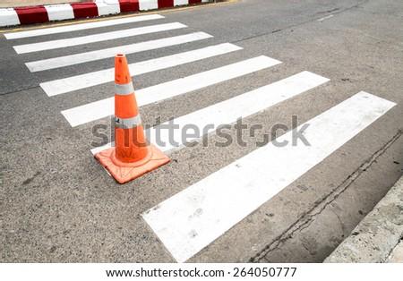 Zebra crossing with traffic cone - stock photo